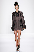 Model walks runway a DESERT SILK GAZAR LINEN MINI CAFTAN W/ EBONY FRENCH LACE + RIBBON TRIMS by Zang Toi, for the Zang Toi Spring 2012 My Dream Of North Africa Collection, during Mercedes-Benz Fashion Week Spring 2012.