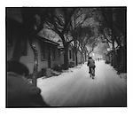 Cyclists wind their way through a snowy &quot;hutong&quot; (alley), Beijing, China.
