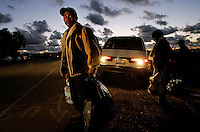 A Migrant worker heads back to his home in McGonigle Canyon after a worship service in Del Mar, Calif. For decades, migrant farmworkers, mostly from Mexico and Latin America, have lived in make-shift  homes in Mcgonigle Canyon and are currently being evicted by a development company who has plans to build homes on the land(AP Photo/Sandy Huffaker)