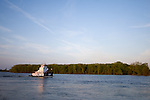 A small towboat floats down the Mississippi River in Clinton, IA, heading for more barges to pick up.