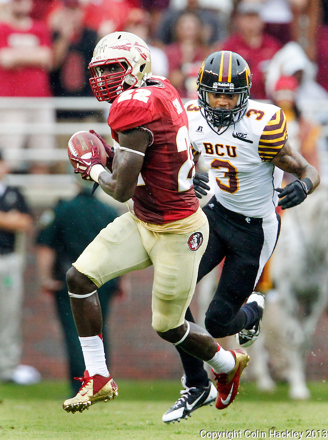 TALLAHASSEE, FLA 9/21/13-FSU-BCC092113CH-Florida State's Telvin Smith tucks away his interception as Bethune-Cookman's Eddie Poole tries to catch him during first half action Saturday at Doak Campbell Stadium in Tallahassee. <br /> COLIN HACKLEY PHOTO