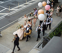 A wedding procecssion marches down Ninth Avenue in Chelsea in New York on their way to their reception, on Saturday, October 17, 2015.  (© Richard B. Levine)