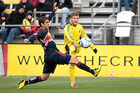 Mar 26, 2011; Columbus, OH, USA; Columbus Crew midfielder/forward Robbie Rogers (18) fires a crossing ball past New York Red Bulls defender Carlos Mendes (44) during their match at Columbus Crew Stadium. The game finished in a 0-0 tie.