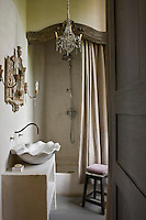 A shower has been built into an alcove in this bathroom with a curtain contained by a carved beam and the washbasin is in the shape of a marble conch shell supported by a stone washstand