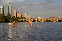 Group of friends in swimsuits sit on stand up paddle boards and wade in the middle of Lady Bird Lake in Austin, Texas.