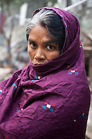Urmila Maurya, 38, poses for a portrait in the street in the institutional area of Lodi Colony, an upmarket area in New Delhi, India on 03 January 2012. A mother of 2, she spends her days on the pavement stringing flowers into garlands for devotees at the nearby Hindu temple. At night, she lays down on the same plastic tarpaulin she uses for the flowers but claims that the police come and tear it up in an attempt to discourage her from squatting in the open. Photo by Suzanne Lee for The National