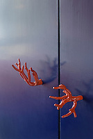 Handles made of coral resemble a pair of hands on this cupboard door