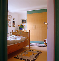 A child's bedroom is simply furnished with a wooden cot bed and a contemporary cupboard