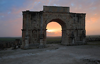 The Triumphal Arch of Caracalla at sunset, built 217 AD by the city's governor Marcus Aurelius Sebastenus at the end of the Decumanus Maximus in honour of Emperor Caracalla, 188-217 AD, and his mother Julia Domna, Volubilis, Northern Morocco. The arch was reconstructed 1930-34 and was originally topped with a bronze chariot pulled by 6 horses. The medallion busts are portraits of Caracalla and Julia Domna. Volubilis was founded in the 3rd century BC by the Phoenicians and was a Roman settlement from the 1st century AD. Volubilis was a thriving Roman olive growing town until 280 AD and was settled until the 11th century. The buildings were largely destroyed by an earthquake in the 18th century and have since been excavated and partly restored. Volubilis was listed as a UNESCO World Heritage Site in 1997. Picture by Manuel Cohen