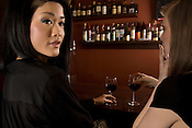 A young caucasian and a Japanese women together at a wine bar.