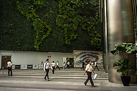 People walk past the Ocean Financial Centre vertical garden in the heart of the Commercial Business District in downtown Singapore. The Vertical Garden at Ocean Financial Centre is the largest potted system vertical garden in the world, as conferred by the Guinness World Records, spanning about 110 metres in length and 20 metres in height. It holds 51,000 pots and 25 plant species, planted in the shape of the world map. Photo by Suzanne Lee/Panos Pictures