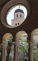 Cloister, built in late Romanesque style by Mihoje Brajkov of Bar in 1360, with view to the bell tower, at the Franciscan monastery on Stradun or Placa, Old Town, Dubrovnik, Croatia. The cloister consists of a colonnade of pairs of 8-sided columns with different capitals, portraying human heads, animals, grotesques and floral motifs. The city developed as an important port in the 15th and 16th centuries and has had a multicultural history, allied to the Romans, Ostrogoths, Byzantines, Ancona, Hungary and the Ottomans. In 1979 the city was listed as a UNESCO World Heritage Site. Picture by Manuel Cohen