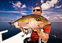 Fisherman in his 40s holding an Amberjack (Seriola rivoliana), a member of the carangide family found in all temperate waters. Shot taken at the Maldives in November 2008, Indian Ocean