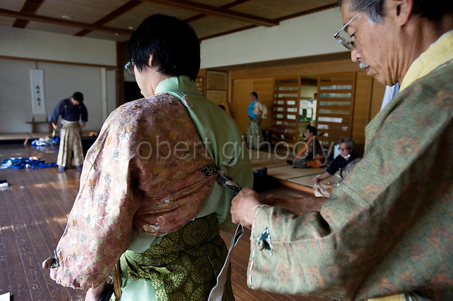"""Kaoru Murata  is given a helping hand by Akimasa Matsumoto to don  traditional attire prior to the """"yabusame-shinji"""" horseback archery ritual on the final day of the Reitaisai grand festival at Tsurugaoka Hachimangu shrine in Kamakura, Japan on  14 Sept. 2012. The yabusame ritual is performed by members of the Ogasawara school, which began mounted archery rituals in the 12th century. .Yabusame was originated in middle of 6th century as a Shinto ritual. Today there are various styles and manners of Yabusame inherited by different shrines and particular families. It was common in the ancient past that the result of Yabusame depended on the number of targets successfully hit, and also fragments of the target were used to tell fortunes. The target and arrows used in successful shots were kept as amulets. The initiation of Yabusame in Tsurugaoka Hachimangu was 1186. Photographer: Robert Gilhooly"""