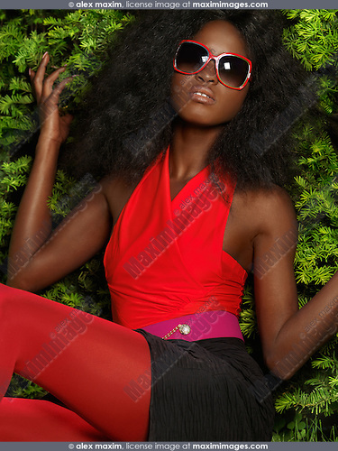 Young stylish black woman in bright red clothes and sunglasses leaning