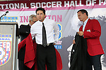 10 October 2013: 2013 inductee Joe-Max Moore (center) is helped into his red jacket by Hank Steinbrecher (left) and Eric Wynalda (right). The 2013 National Soccer Hall of Fame Induction Ceremony was held on the West Plaza outside Sporting Park in Kansas City, Kansas.