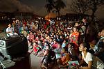 A crowd gathers to wath a natural hostory film, Komodo Village, Komodo National Park