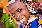 This Fulani girl from Bele Kwara, Niger has walked 10 kilometers to attend the weekly market in the town of Torodi.  She sports the traditional Fulani facial scarring that is considered beautiful. The scarring is done with a razor blade, and charcoal powder mixed with cream is rubbed into the fresh wound to create the darkened effect.  These are not rites of passage - she chose to have it done, because it is considered beautiful.