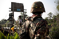 Thai soldiers in the border village of Wale watch the bridge that marks the border. Burmese refugees had begun to return home after less than three days in Thailand. An estimated 20,000 had fled into Thailand to escape clashes in the border towns of Myawaddy and Pyaduangsu, only a day after a Burmese election which critics described as a sham..Ethnic minorities along the Thai-Burma border had warned earlier that the junta would launch a major offensive after the election, as many armed rebel groups had refused to become part of the government-controlled Border Guard Forces.&nbsp;