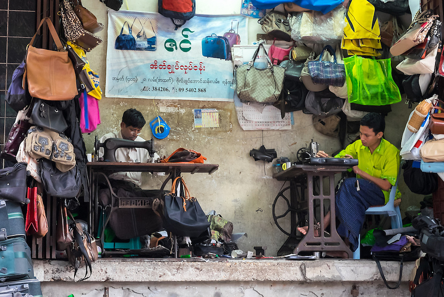 YANGON, MYANMAR - CIRCA DECEMBER 2013: Merchants repairing and selling bags in street market of Yangon