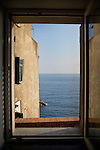 Photo looking out a window at the sea in Riomaggiore, Italy.