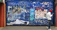 Teenager with red cap and white sweat typing on his cell in front of a blue double gate covered with spray paint graffiti and posters, Brick Lane area, London, UK. Picture by Manuel Cohen