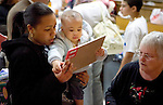 TORRINGTON, CT- 04 JANUARY 2008 --010409JS02-Alejandrina Pascual of Torrington, and her 16-month-old son Freiny Francisco, pick out a gift with the help of church volunteer Carol Bushy, right, during the annual Three Kings Day celebration Sunday at Trinity Episcopal Church in Torrington. <br /> Jim Shannon / Republican-American