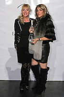 (l) Kristina Cogswell from Luxury is a Necessity, and (r) fashion show producer, pose with a bottle of  U'Luvka Vodka, after the EVa Minge - DNA Minge range Fall/Winter 2011/2012 collection runway show, during New York Fashion Week Fall 2011.