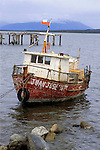 South America, Chile, Puerto Natales. A wood fishing boat with Chilean flag.