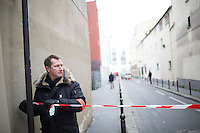 A police officer puts up police tape near the site of the massacre at Charlie Hebdo in Paris where masked gunmen killed 12 people. Paris, France, (Jan. 7, 2015).