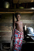 A young girl called Madeleine cooks coconut milk over an open fire, in her family's basic home, in Bain village in the Cape Orford logging concession (run by Rimbunan Hijau- Malaysian logging giants), in Bain, East New Britain Island, Papua New Guinea,  Friday 19th September 2008.