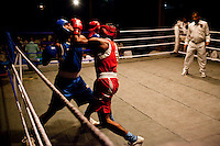 Inter-state boxers fight it out at an all-India invitational boxing competition in the neighbouring town of Burnpur, Calcutta, West Bengal, India. Razia Shabnam, 28, was one of the first women boxers in Kolkata. She was also the first woman in her community to go to college. She is now a coach and one of only three international female boxing referees in India. Photo by Suzanne Lee for Panos London