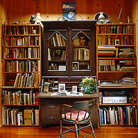 A large antique bureau is flanked by bookshelves overflowing with books and records