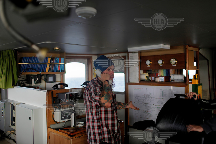 Martti Leinonen, a Greenpeace activist from Finland, 3rd mate on board the Arctic Sunrise, speaks on the phone from the bridge during the ship's European sustainable fisheries tour campaign.