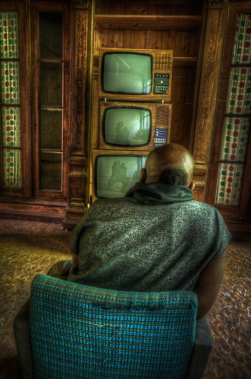 Male figure seated beside old televisions
