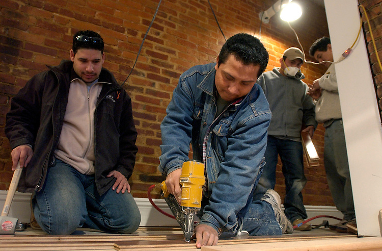 Miguel Mendez installs hardwood floors as Ralph Santos, left, looks on, on the second floor of a townhouse on 6th Street, NW.  The house will be featured on This Old House.