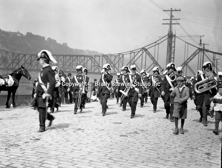 Pittsburgh PA:  Pittsburgh-area Manson marching in the annual St Patrick's Day Parade - 1903.  View of Masonic Band marching down Water Street with children walking along side the troop. The new Wabash Bridge in the Background.