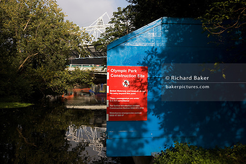 Stratford Olympic Park construction site barrier marks boundary of no access to land near River Lea in East London.