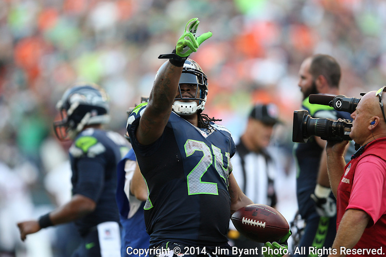 Seattle Seahawks running back Marshawn Lynch points to the crowd and is surrounded by television cameramen after scoring the winning touchdown against the  Denver Broncos in overtime at CenturyLink Field in Seattle, Washington on September 21, 2014. The Seahawks won 26-20 in overtime.      ©2014. Jim Bryant Photo. All rights Reserved.