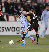Sporting Kansas City midfielder Roger Espinoza (15) shields the ball against D.C. United midfielder Perry Kitchen (23) . Sporting Kansas City defeated D.C. United  1-0 at RFK Stadium, Saturday March 10, 2012.