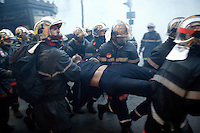 25 March 2004 - Paris, FRA - Firefighters carry an injured colleague to safety during a violent clash with riot police.in Paris, France, 25 March 2004. The firefighters earlier marched through the city to demand that their profession be classified as a dangerous occupation which entails various social security benefits including early retirement. The violence near the Paris Opera house left 2 firefighters and 20 policemen injured.