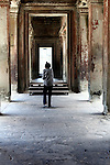 A woman walks down at empty corridor inside the central temple complex at Angkor Wat, Cambodia. June 7, 2013.