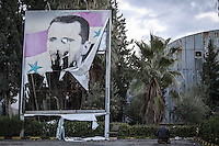 In this Saturday, Dec. 08, 2012 photo, a Syrian rebel fighter offers evening prayers beside a ripped sign of president Bassar Al-Assad during heavy clashes in Aleppo, Syria. (AP Photo/Narciso Contreras)