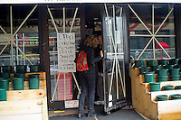 A customer waits in line at a deli, one of the few open because of the power outage, in the New York neighborhood of Tribeca after Hurricane Sandy, seen on Tuesday, October 30, 2012. Hurricane Sandy roared into New York disrupting the transit system and causing widespread power outages. Con Edison is estimating it will take four days to get electricity back to Lower Manhattan. (© Frances M. Roberts)