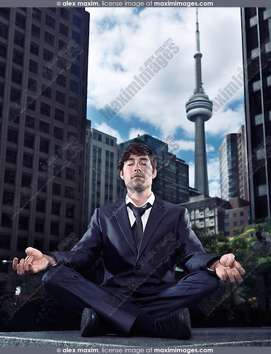 Conceptual portrait of a businessman sitting crosslegged meditating outdoors in downtown Toronto with CN tower and office buildings in the background. Meditation and busy urban lifestyle concept. Canada.
