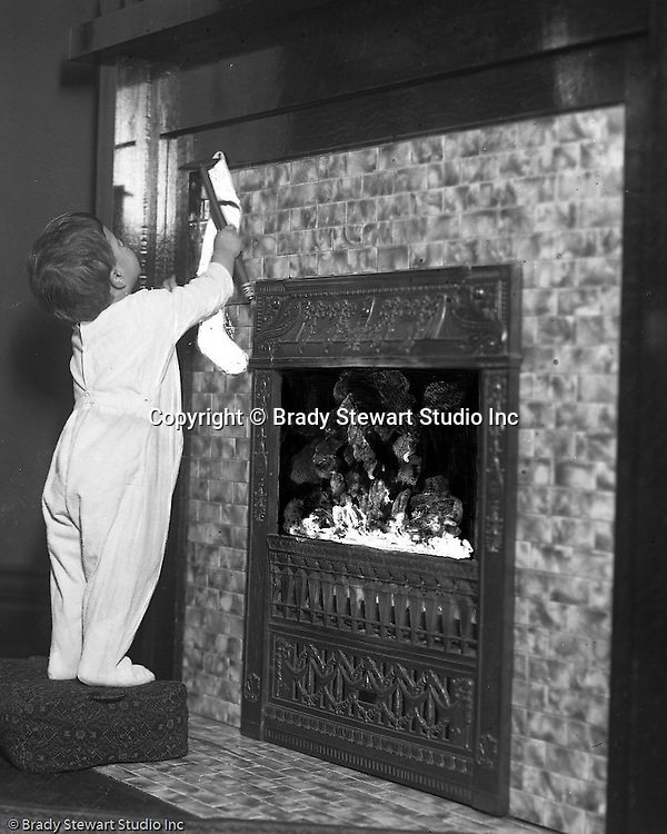 """Wilkinsburg PA:  Helen Stewart hanging a Christmas Stocking - 1918.  Brady Stewart etched on the emulsion side of the film to create a """"fire"""" effect in the fireplace."""