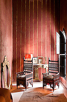 Sunlight streams in through the wooden shutters into the exotic bedroom with red and gold striped walls and a pair of carved wooden chairs