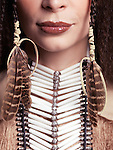 Artistic closeup portrait of a woman wearing aboriginal native accessories necklace and feathers in her hair. Close up of lips.