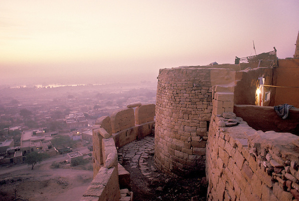 JAISALMER, INDIA : The outer walls and turrets of Jaiselmeer Fort. Jaisalmer fort was built in 1156 and is the second oldest in Rajasthan. Two hundred and fifty feet tall and reinforced by an imposing crenellated sandstone wall 30 feet high, it has 99 bastion, 92 of which were built between 1633 and 1647. Wells within the fort still provide a regular source of water.