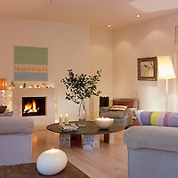A circular coffee table on a base of marble blocks is the centrepoint of a comfortable living area lit with candles and fairylights around a contemporary fireplace